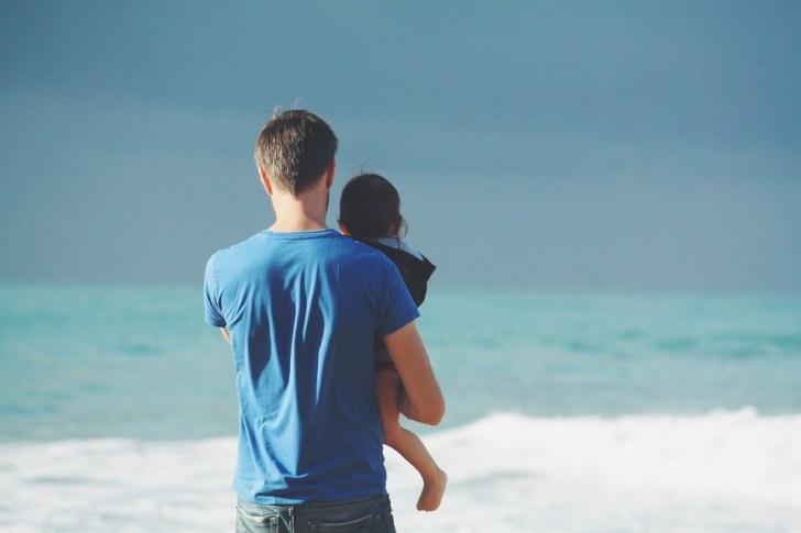 砂浜にたたずむ父と息子