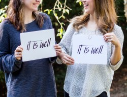 "Two young females holding signs saying ""It is Well."""