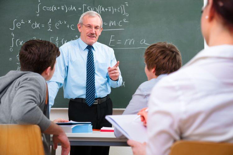 Professor teaching in class in front of a chalkboard