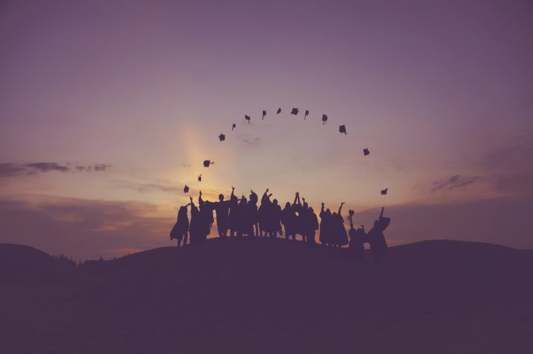 graduates' silhouette against the sunset