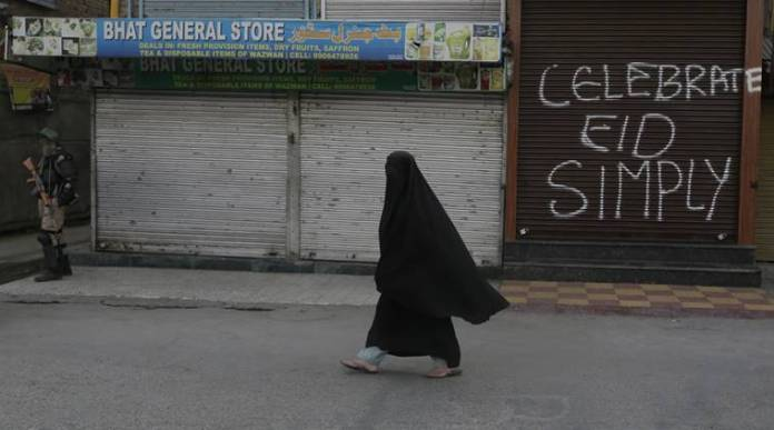 A veiled Kashmiri woman walks past a graffiti on a closed shop at a deserted market during a continuing strike in Srinagar, Indian controlled Kashmir, Sunday, Sept. 11, 2016. Kashmir remained under security lockdown and separatist sponsored shutdown after some of the largest protests in recent years were sparked by the killing of a popular rebel commander on July 8. (AP Photo/Mukhtar Khan)