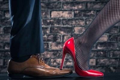 赤いハイヒールの女性が男性の革靴を踏んでいる