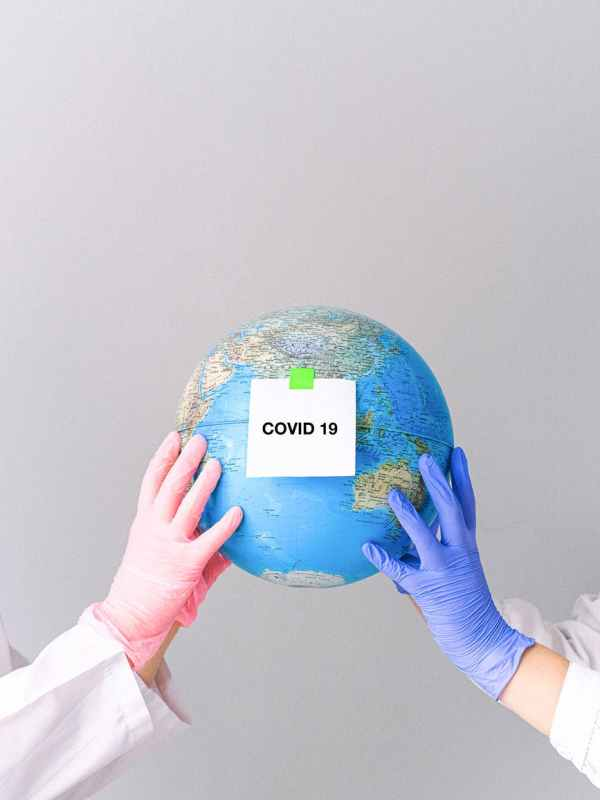 hands with latex gloves holding a globe