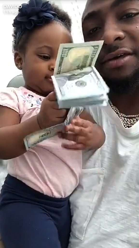 Money League! Davido Share Photos Of His Cute Daughter Playing With $100 Bills 2