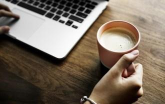 パソコンのマックと牛乳が入ったマグカップの画像