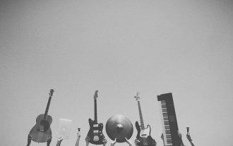 手に持ったギターなどの楽器を掲げている画像