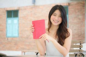 赤い本を携えて微笑む、留学生の女子大生