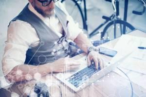 男性がノートパソコンを使って調べ物をしている