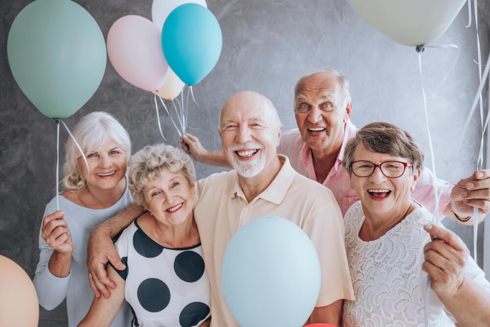 外国人の老人たちが集まって、風船を持っている