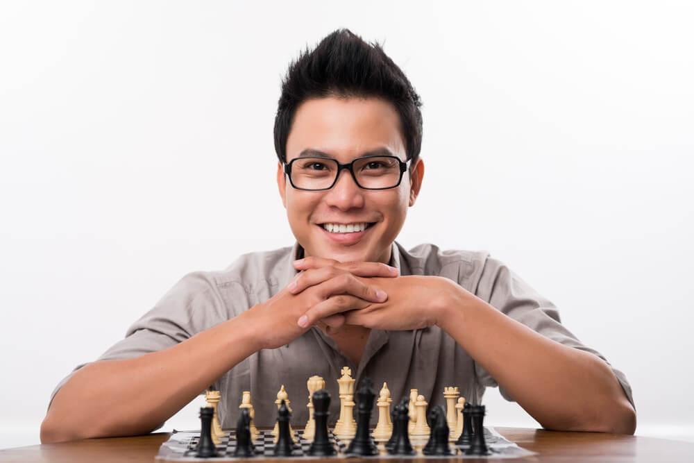 チェスの盤面前で微笑む男性