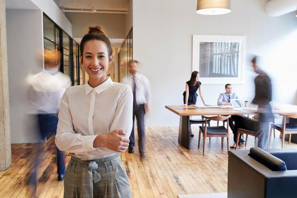 「永住権取得の要件は?」「永住ビザを取得するためには3要件必要」忙しいオフィスで元気に働く外国人女性