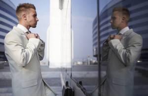 鏡に映る自分自身の姿を見つめる男性