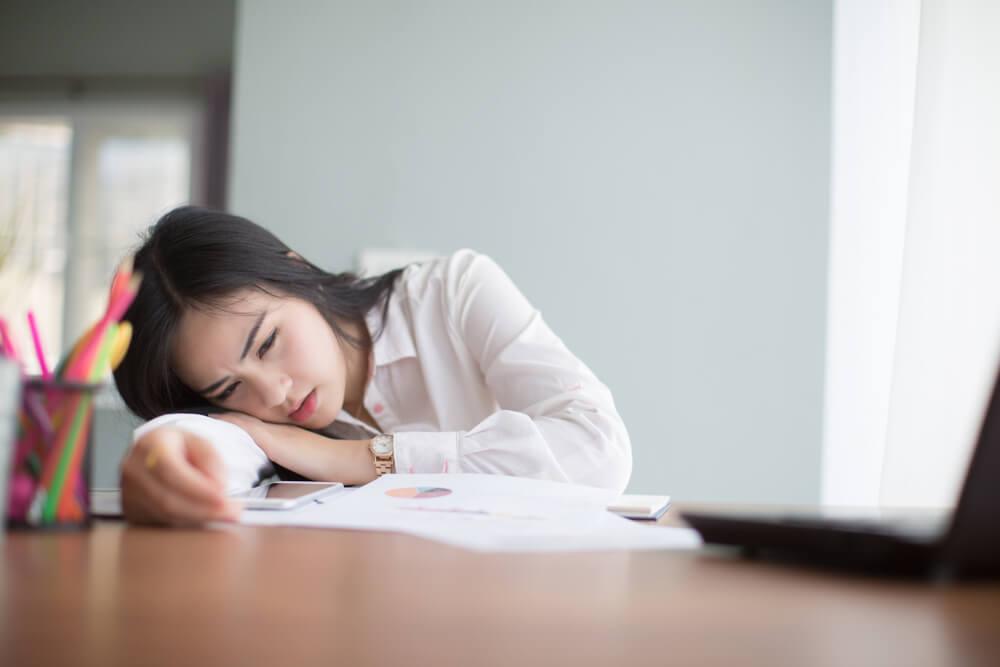 疲れて机に突っ伏している若い女性