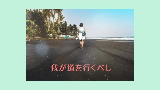 海辺を歩いていく後ろ姿の女性