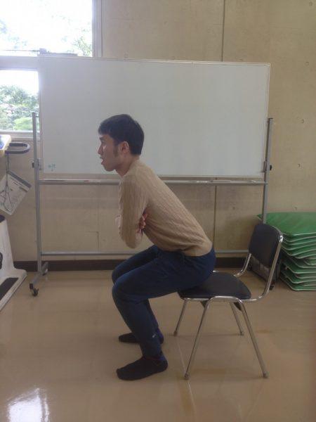 パイプ椅子に座る男性