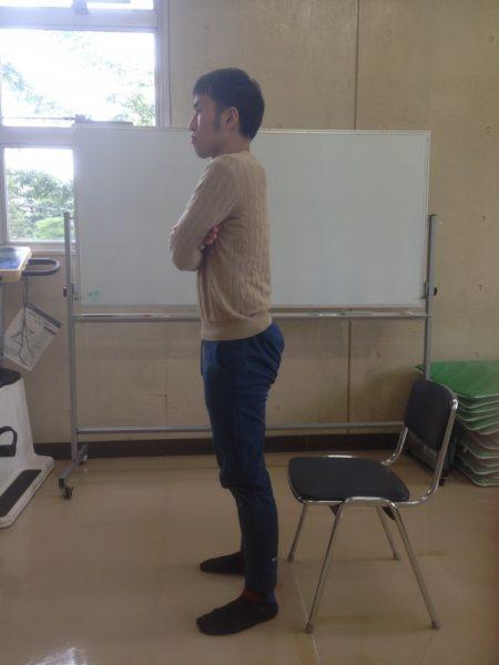 パイプ椅子の前で手を組んで立つ男性