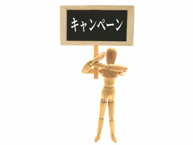 キャンペーンの看板をもつ木製人形