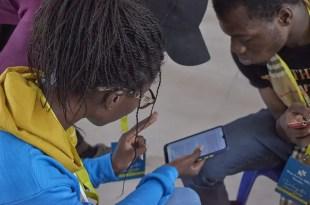 De jeunes Nigérians discutent du contenu d'une page Web ouverte sur un smartphone. Image de James Moore200 via Wikimedia Commons, 27 mars 2021, sous licence CC BY-SA 4.0.