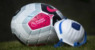 Un ballon de football et un masque visage du Covid-19 sur la pelouse d'un terrain de foot.