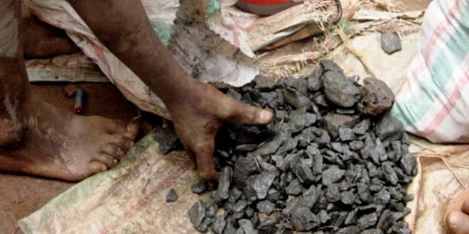 Une main touchant le minerais de la RDC.