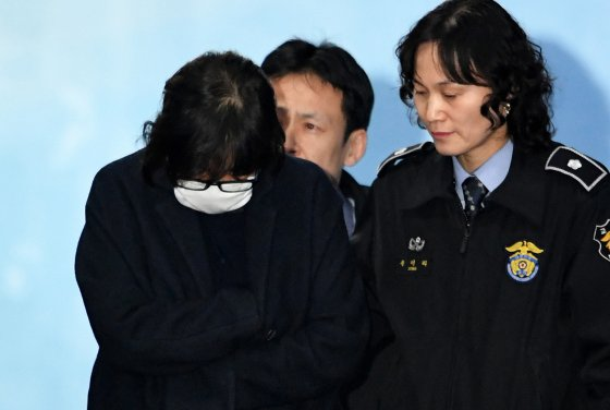 Choi Soon-Sil, front left, is escorted following her formal arrest in Seoul on Nov. 3, 2016.jpg