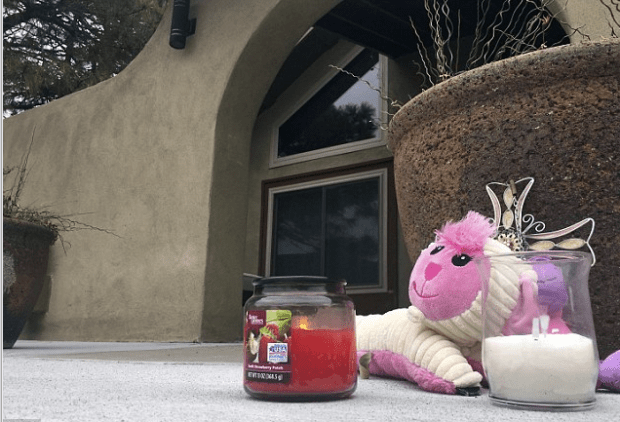 Memorial of a stuffed animal and candles left by neighbors sits outside an Albuquerque home where three siblings, ages 5, 6 and 9, were shot dead Monday night .png