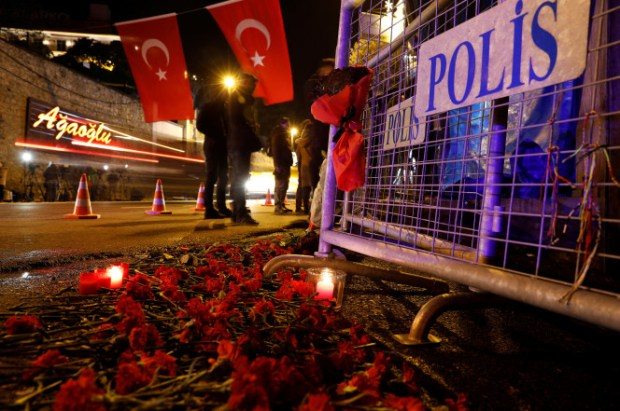 Flowers are placed in front of a police barrier near the entrance of Reina nightclub1.jpg