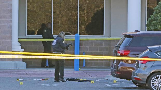 Investigators inspect he spot wher the first officer was shot1.jpg