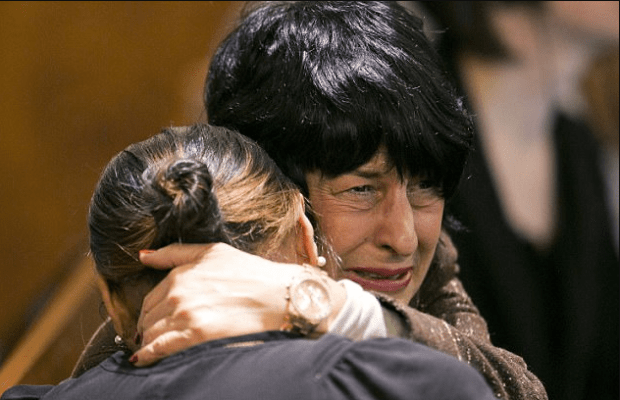 Hernandez's fiancee Jenkins and Hernandez's mother Terri hug in court back in April 2015 as the guilty verdict is read during his 2015 murder trial.png