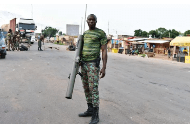 A mutinous soldier poses with a weapon in the streets of Bouake, on Sunday May 14, 2017.jpeg