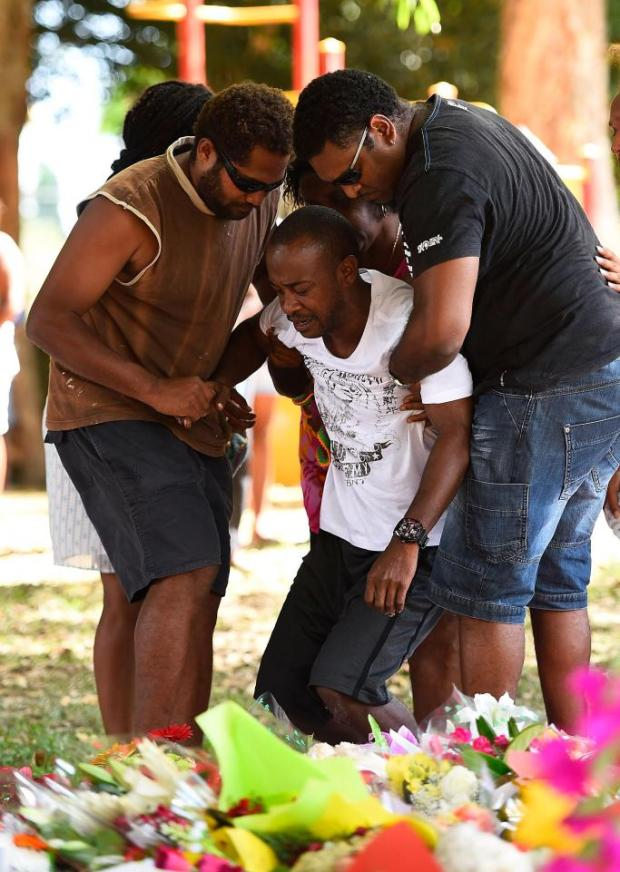Family members mourn at the scene of a memorial set up in a nearby park in 2014