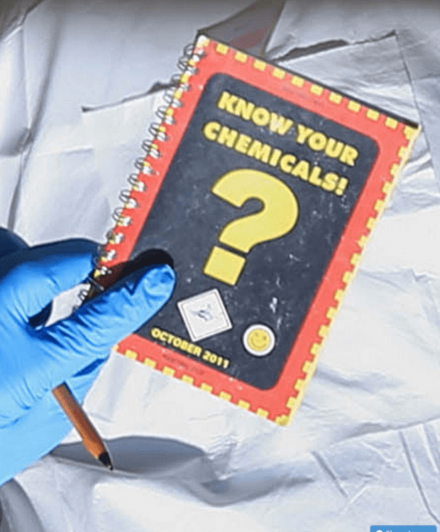 Investigator clutching a 'know your chemicals' manual found at the brothers' home.png