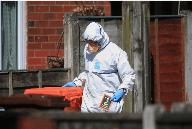 Police forensics officer seen leaving the suspect's home holding a bomb making manual.png