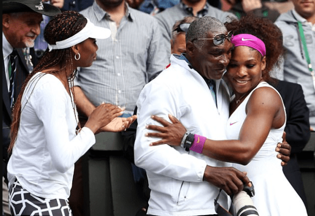 Venus [left], applauds as Richard Williams [center], hugs Serena after her Wimbledon singles championship in 2012.png
