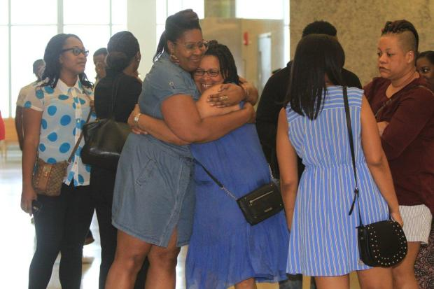 Eunice Ashley Henry, (c.) mother of murder victim Omar Murray, hugs her niece Nicole Barten1.jpg