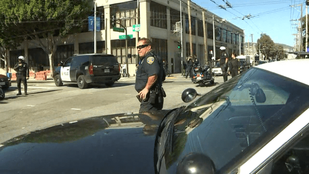 Police divert traffic away from the UPS warehouse and customer service center in San Francisco on Wednesday during the shooting.png