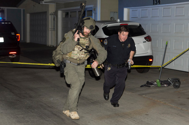 A SWAT officer and a Seal Beach officer run down an alley after reports of shots.jpg