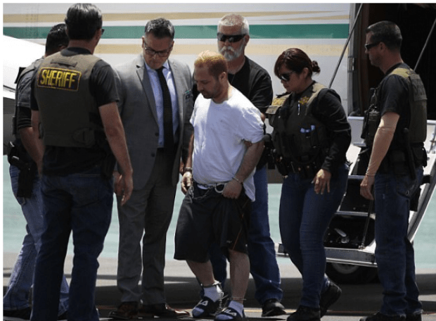Andressian is escorted off a plane in shackles after landing at the Long Beach Airport on Friday .png