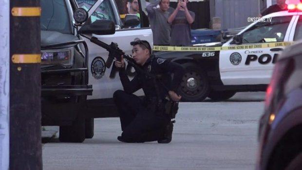 police takes cover behind squad car during the stand off.jpg