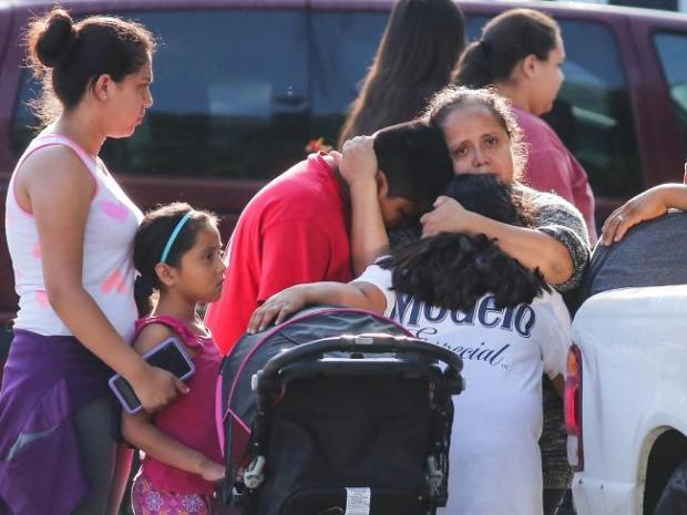 Shocked neighbours embrace near the home where a family was stabbed.jpg