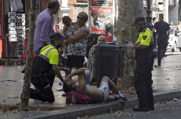 A man lying on the street in Barcelona after the van ploughed into pedestrians along Las Ramblas .png