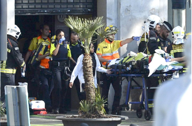 A person is stretched out of a mall by medical staff in a cordoned-off area in Barcelona after the van ploughed into pedestrians along Las Ramblas .png