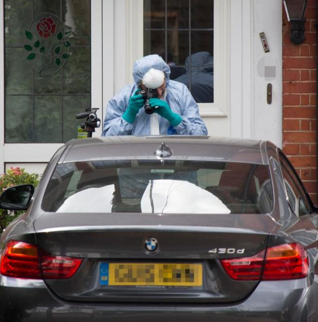 Investigator photographs a car parked outside the house where a mother and daughter were fatally stabbed