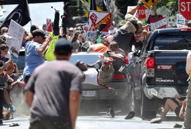People fly into the air as a vehicle drives into a group of protesters demonstrating against a white nationalist rally in Charlottesville, Va., Saturday, Aug. 12,.jpg