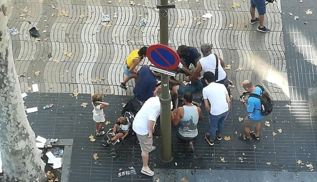 People gather round a victim after the van drove into a crowd in Barcelona.jpg