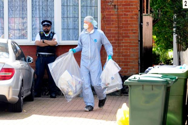 Police Forensics team removing items from the house in North London in evidence bags