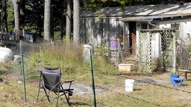 A pair of small burn piles sit behind a residence .jpg