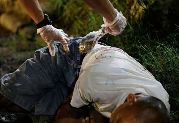 Cop removes a bag of marijuana from the pocket of one of two drug suspects after they were shot dead by police as they tried to evade a checkpoint in Quezon city