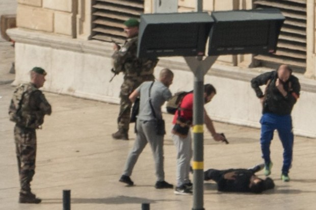French security officers secure the suspect at the Marseille railway station after the stabbing incident Sunday