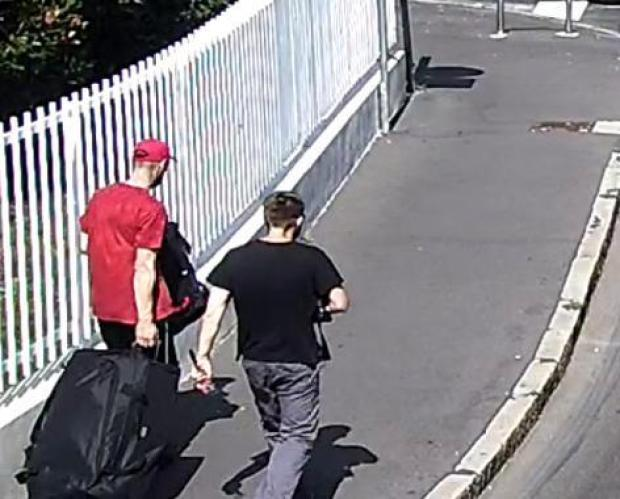 Lukasz and Michal Herba strolling away from kidnap joint with heir suitcase